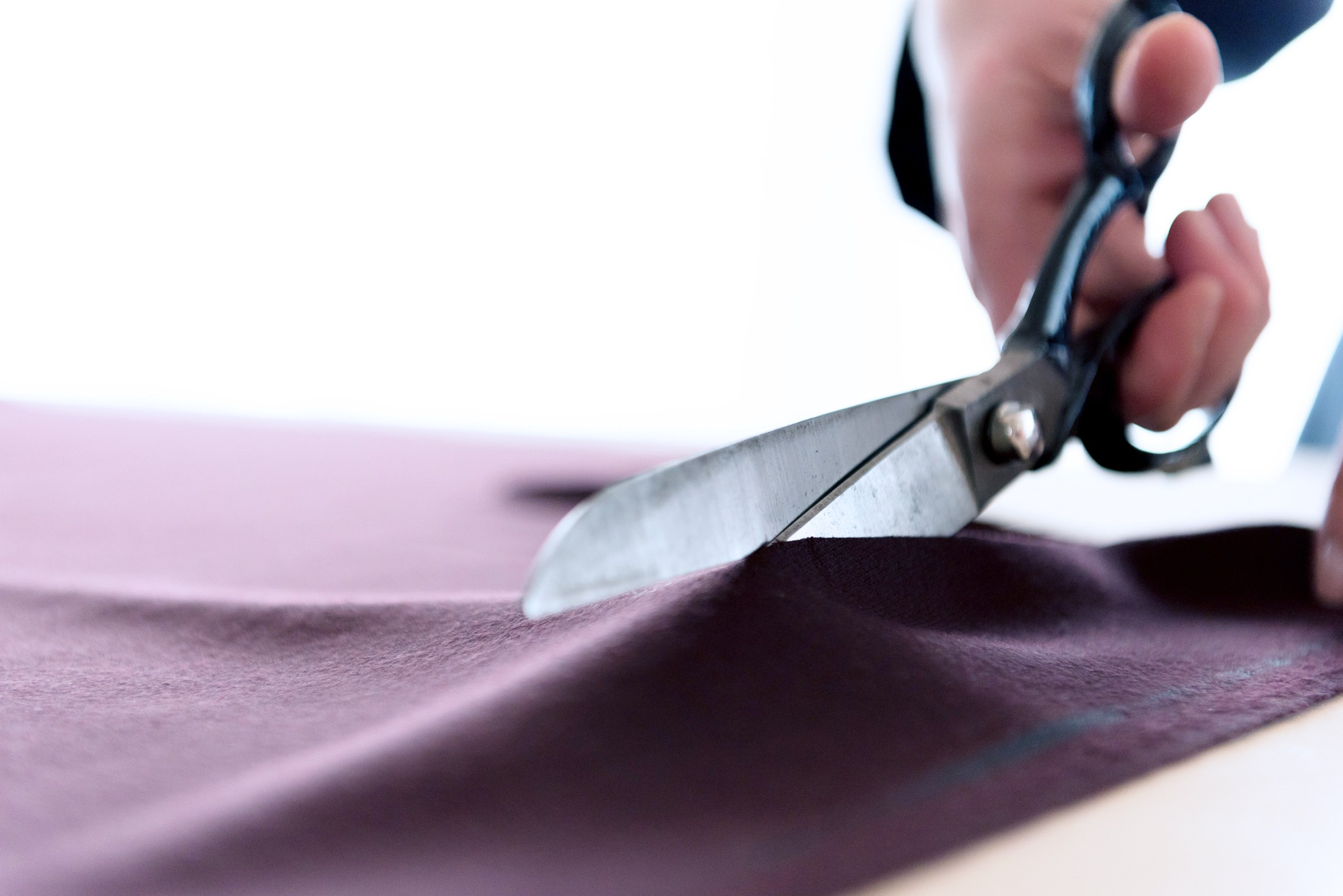 Close up of cutting shears being held and cutting through burgundy cloth