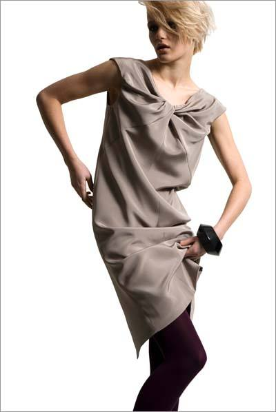 Model wearing a beige silk crepe dress with twisted front neckline by Dara Ford