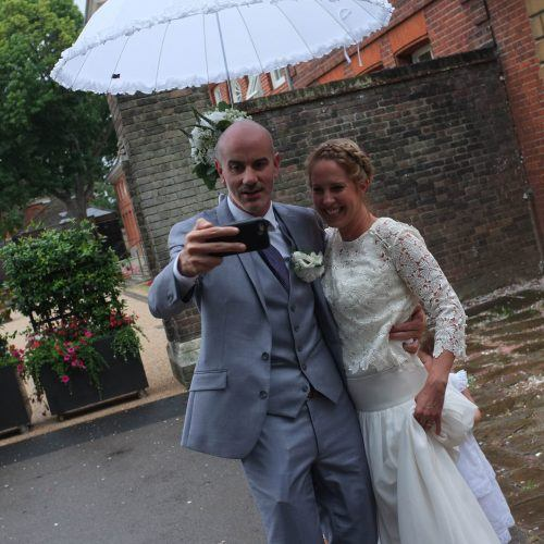Wedding couple standing under and umbrella and pictured taking a selfie