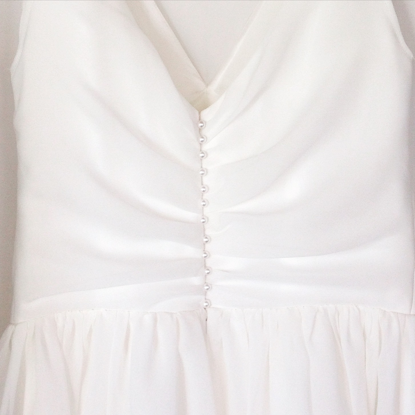 Row of pearl buttons on ivory georgette wedding dress