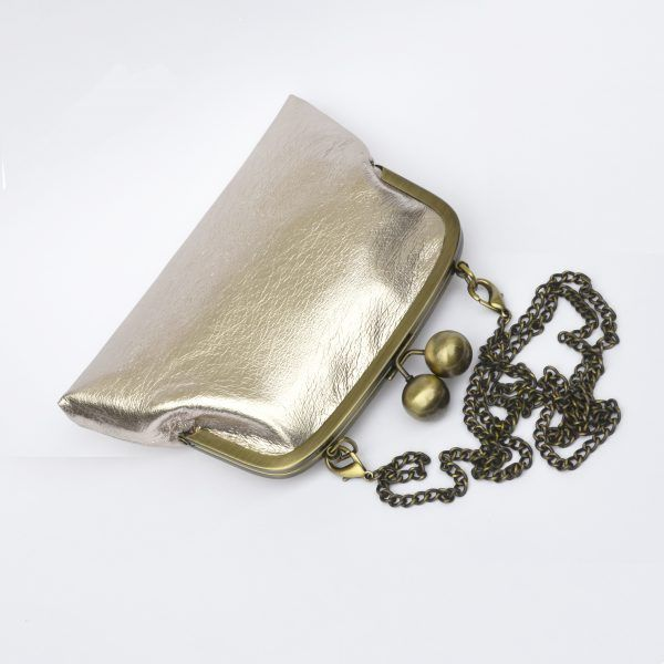 Birdseye view of blush champagne foil clutch purse with chain strap.