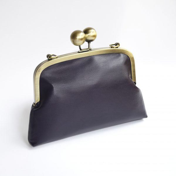 Dark purple clutch bag with brass kiss lock closure