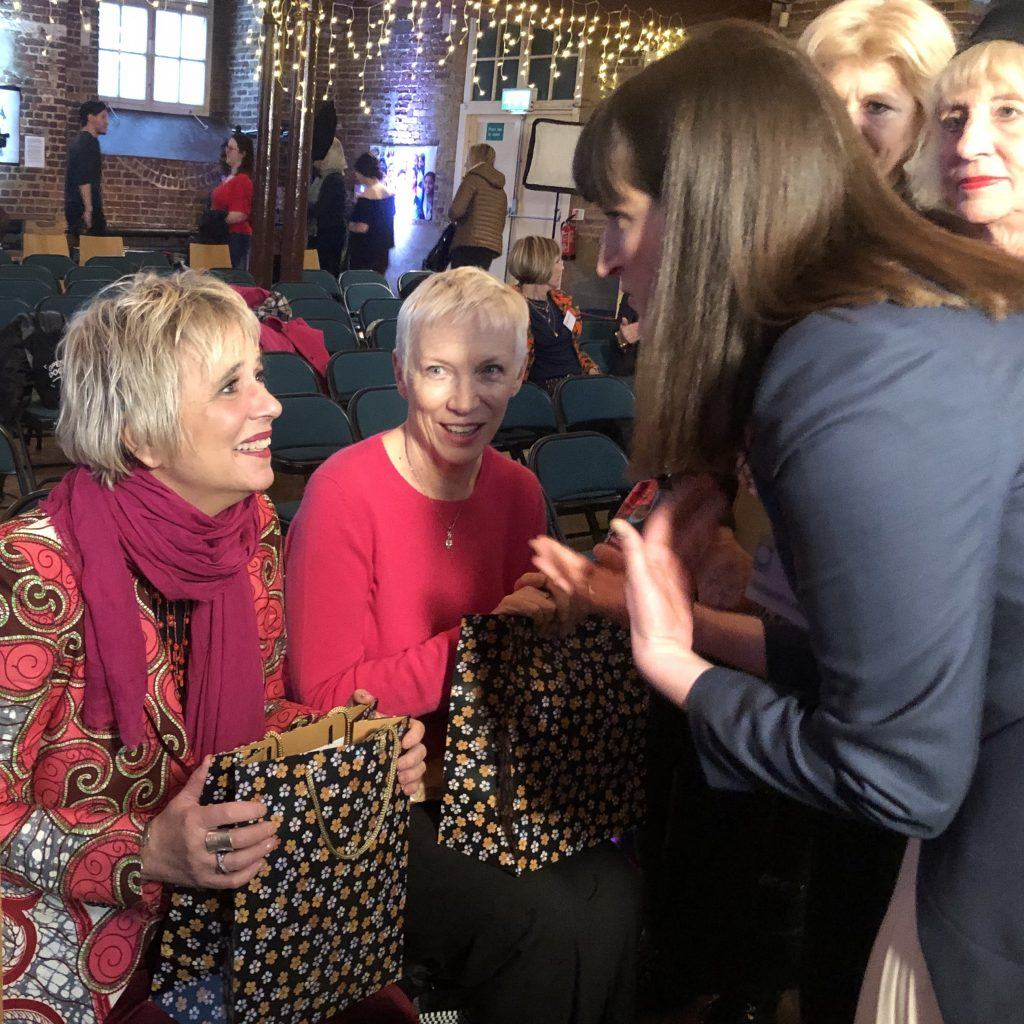 Women's tailor Dara Ford speaking to Eve Ensler and Annie Lennox and gifting them silk scarves from her own collection