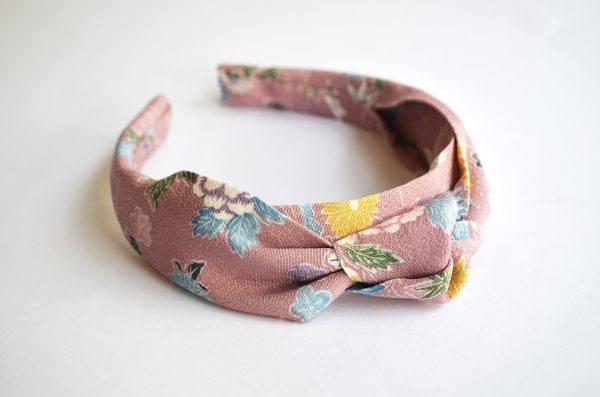 Close up of pink knot headband lying flat on a white background